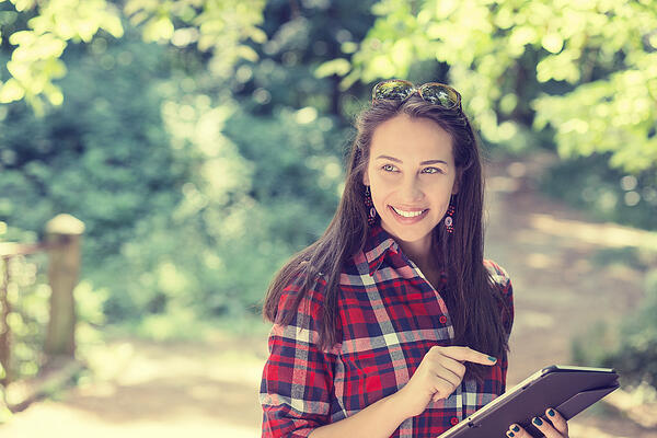 Closeup portrait attractive happy casual woman using pc isolated on park outdoors tree background. Positive human emotion feelings. Technology in modern life concept-1