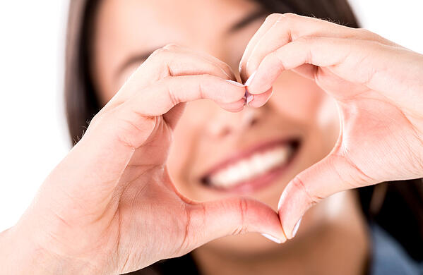 Woman making a heart shape with her hands - isolated over white
